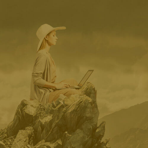 Woman writing on a computer on a mountaintop